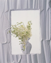 White plaster frame with white plaster vase in center filled with white flowers von Panoramic Images