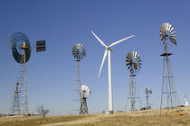 Traditional windmills with a wind turbine on a landscape by Panoramic Images
