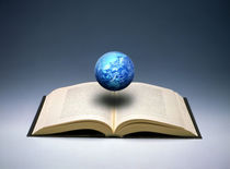 Small cloud filled globe hovering above open book von Panoramic Images