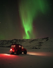 Jeep in a snow covered field with Aurora Borealis in the sky von Panoramic Images