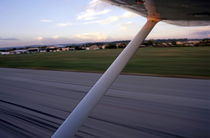 Wing of a private plane landing at the airport by Sami Sarkis Photography