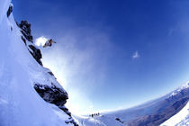 Snowboarder jumping off a mountainside. by Ross Woodhall