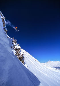 Extreme skier jumping off a cliff by Ross Woodhall