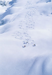 Skiers turning off piste. by Ross Woodhall