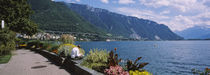 Rear view of a man sitting at the lakeside, Lake Geneva, Montreux, Switzerland von Panoramic Images