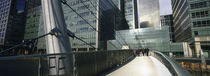 Bridge in front of buildings, Canary Wharf, London, England by Panoramic Images