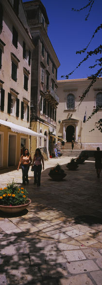 Two women walking in front of a courtyard in Corfu Old Town, Corfu, Greece von Panoramic Images