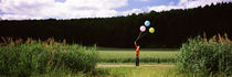 Woman holding balloons and standing in the field, Baden-Württemberg, Germany von Panoramic Images