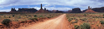 Dirt road through desert landscape with sandstone formations, Utah. by Panoramic Images