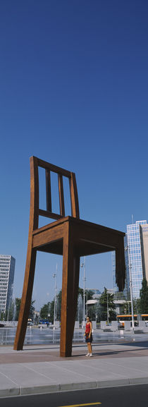 Woman standing under a sculpture of large broken chair, Geneva, Switzerland von Panoramic Images