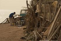 Ein Mann bei der Surfbrett-Reparatur in der Westsahara von Andy Fox