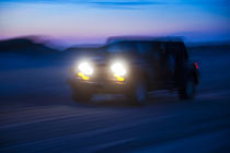 SUV riding off road at night. by John Greim
