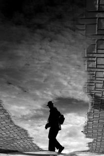 Man reflected in a puddle of water by Ramon Cami