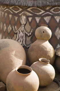 Handcrafted pottery leaning against traditional mud dwelling in Sirigu painted village von Danita Delimont