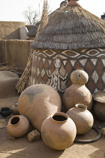 Handcrafted pottery leaning against traditional mud dwelling in Sirigu painted village by Danita Delimont