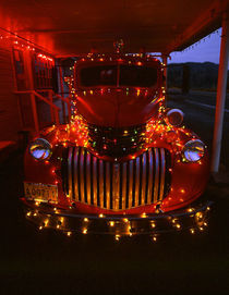 Vintage fire truck decorated with lights at Christmas von Danita Delimont