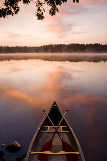 A canoe rests on the shore of Pawtuckaway Lake at dawn as seen from Horse Island in New Hampshire's Pawtuckaway State Park von Danita Delimont
