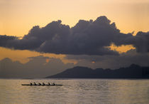 An outrigger canoe team practices off the coast of the island of Tahiti as the sun sets over the island of Moorea in the Society Islands of French Polynesia by Danita Delimont