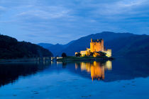 Beautiful Eileen Donan Castle in Western Dornie in Highlands os Scotland the most photographed castle in the world at night with reflections on still beautiful waters by Danita Delimont