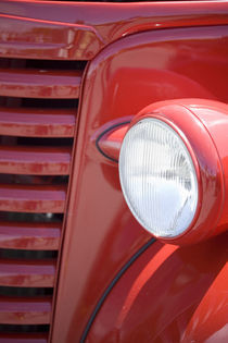 Headlight and partial grill of a red antique truck von Danita Delimont