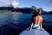 Woman enjoying view on bow of boat wearing flower garland by Danita Delimont