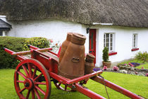 Metal containers on cart and thatched roof cottage by Danita Delimont