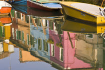 Boats on a canal with reflections of colorful houses on the water by Danita Delimont