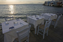 Three dinner tables overlooking the sea at sunset by Danita Delimont