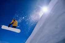 Man flying through the air on a snowboard with the sun over his shoulder in the Wasatch Mountains of northern Utah by Danita Delimont
