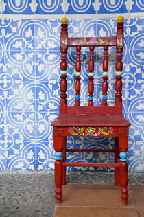 Typical blue tile walls with red chair by Danita Delimont
