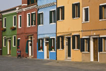 Colorful row of homes and empty street by Danita Delimont