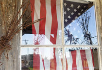 Flag in window next to coil of barbed wire by Danita Delimont