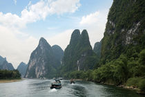 River boats line the way along the River with it's dramatic mountains by Danita Delimont