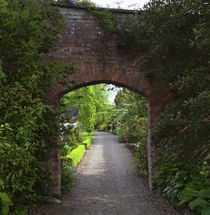 The Dromoland Castle very green walled garden path through a brick archway by Danita Delimont