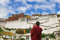 Tibetan monk with Potala Palace (MR) by Danita Delimont
