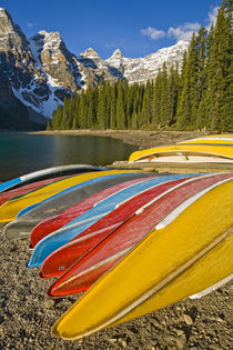 Moraine Lake and rental canoes stacked on shore von Danita Delimont