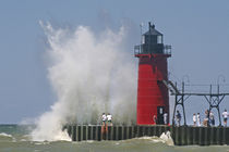 People on jetty watch large breaking waves in South Haven Michigan by Danita Delimont