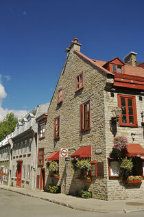 An old stone building housing a restaurant forms the corner of a block in Old Quebec City by Danita Delimont