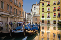 Gondolas moored along canal by Danita Delimont