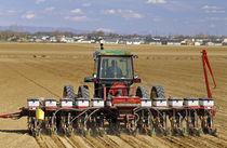 Tractor pulling a seed corn planter von Danita Delimont