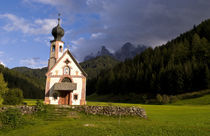Beautiful isolated lonely church called Rainui in valley in the Italian Dolomites village of Val Di Funes mountains Alpine area of Italy with Dolomites looming behind von Danita Delimont