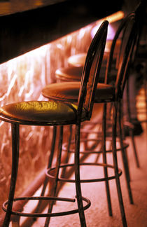 Barstools in pink light by Danita Delimont