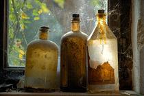 Nostalgie - drei alte verstaubte Glasflaschen am Fenster von Matthias Hauser