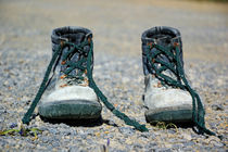 Pair of used work boots on road by Sami Sarkis Photography