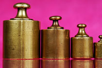 Copper weights on pink background by Sami Sarkis Photography