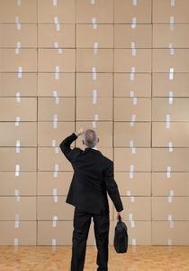 Businessman facing a cardboard boxes wall by Sami Sarkis Photography
