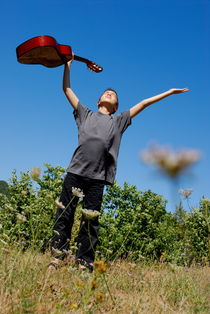 Boy standing in meadow with guitar by Sami Sarkis Photography