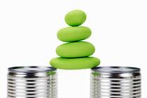 Stack of green pebbles balancing between tin cans von Sami Sarkis Photography
