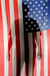 Silhouette of man behind US Flag by Sami Sarkis Photography