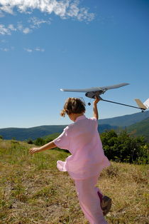 Girl (6-7) flying model plane in field von Sami Sarkis Photography